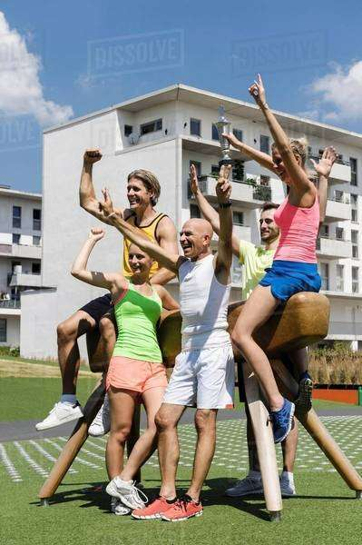 Exercise group cheering next to pommel horse in park Royalty-free stock photo