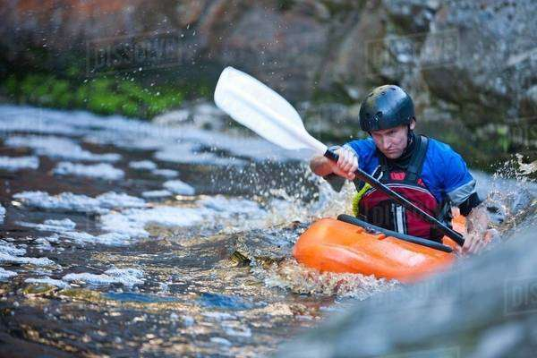 Mid adult man kayaking on river rapids Royalty-free stock photo