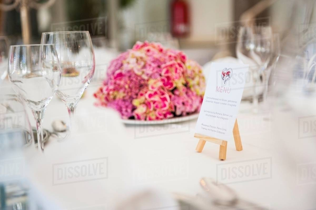 Table with wine glasses, menu and flower arrangement at wedding ...