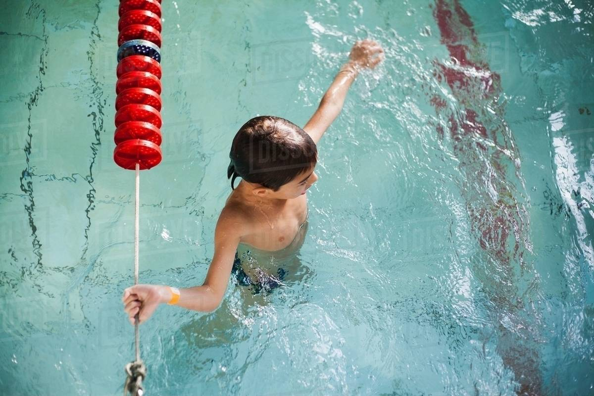 High angle view of boy holding onto rope in swimming pool stock photo