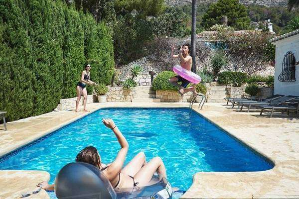 Mature woman with son and daughter playing in apartment swimming pool Royalty-free stock photo
