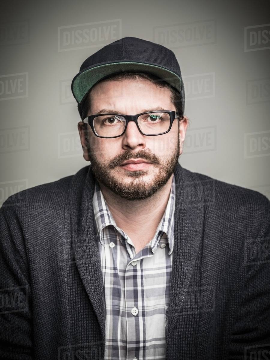 58982a66418 Head and shoulder studio portrait of bearded young man wearing spectacles  and baseball cap