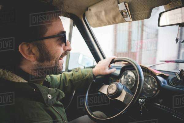 Mid adult man smiling whilst driving vintage car Royalty-free stock photo