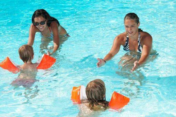 Women teaching to kids how to swim Royalty-free stock photo