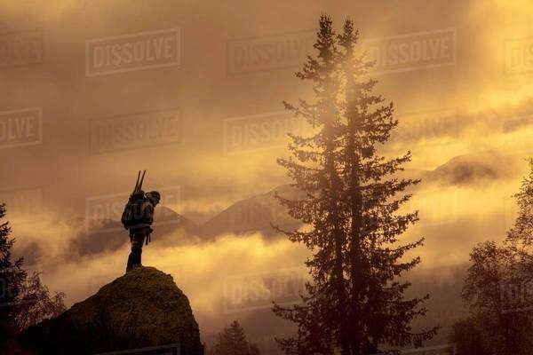 Silhouetted view of male looking down from rock at sunset, Ural, Russia Royalty-free stock photo