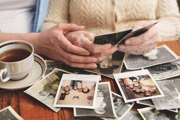 Senior woman and granddaughter sitting at table, looking through old photographs, mid section Royalty-free stock photo