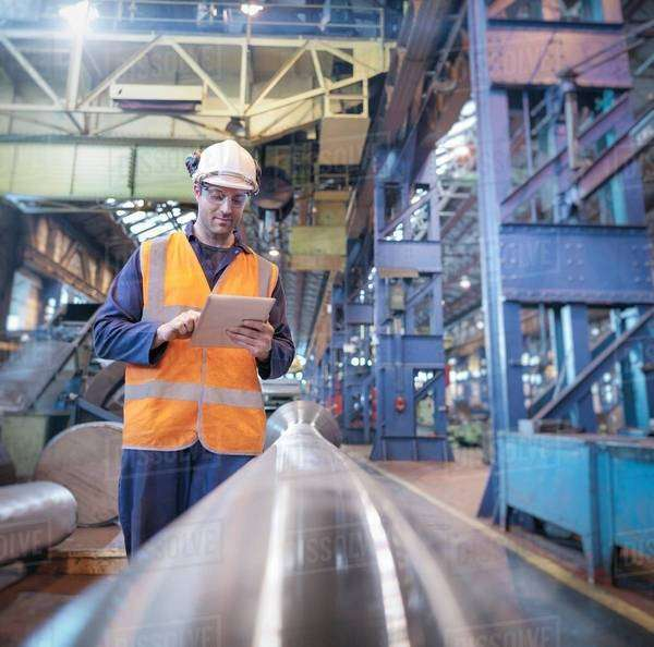 Engineer checking steel part with digital tablet in engineering factory Royalty-free stock photo