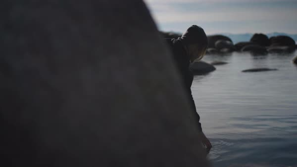 A sliding shot from behind a boulder that reveals a young woman gracefully touching the water of a still, mountain lake. Royalty-free stock video