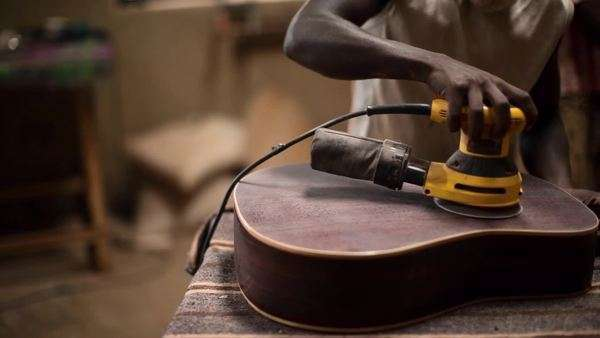 Medium close-up shot of luthier polishing a guitar Royalty-free stock video