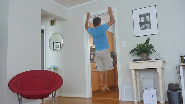 Funny clip from real time to timelapse of man using door frame as an exercise devise for pull ups workout. Royalty-free stock video