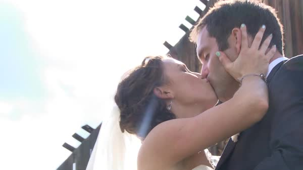 Model released bride and groom kiss each other on their wedding day outside old country barn. Royalty-free stock video
