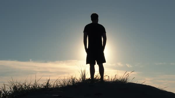 Man standing on sand dune overlooks the sunny blue sky at the Oregon Coast on beautiful day then walks away, out of frame. Royalty-free stock video