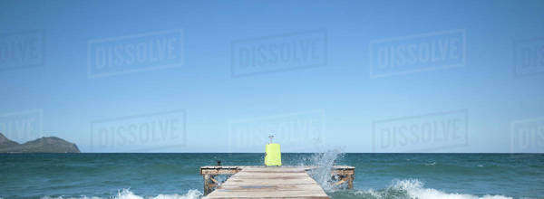 Waves crashing against dock, yellow suitcase at end of dock Royalty-free stock photo