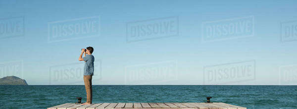 Man standing on pier looking at ocean view through binoculars, side view Royalty-free stock photo