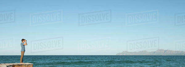 Man in distance standing on pier looking at ocean view through binoculars Royalty-free stock photo