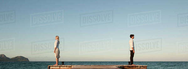 Couple standing back to back on pier, side view Royalty-free stock photo