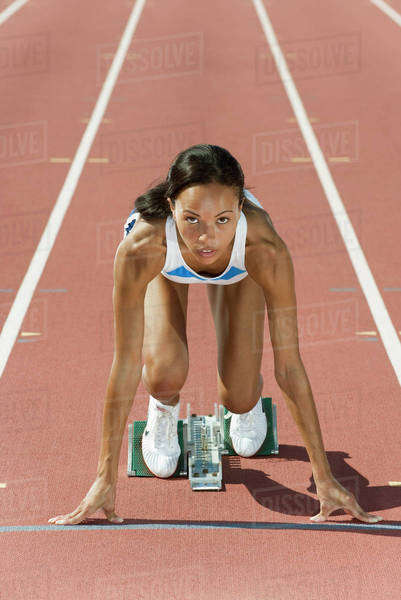 Woman crouched in starting position on running track Royalty-free stock photo