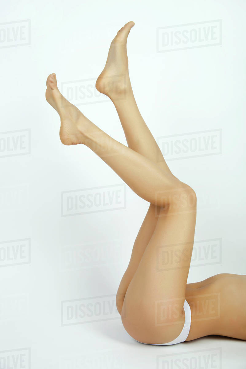 Semi-nude woman lying on back with legs in air, low section