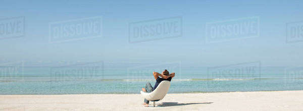 Man relaxing in chair on beach, rear view Royalty-free stock photo