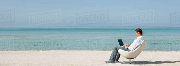 Man using laptop computer at the beach Royalty-free stock photo