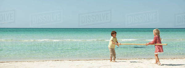 Children carrying bamboo together at the beach Royalty-free stock photo