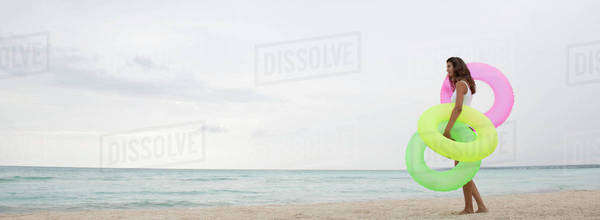Woman standing on beach, holding inflatable rings, side view Royalty-free stock photo