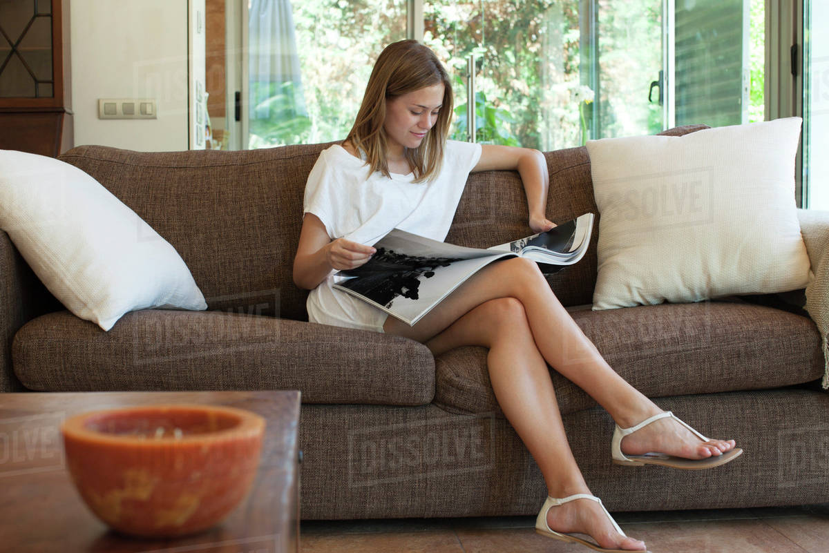 Woman Relaxing On Sofa With Magazine