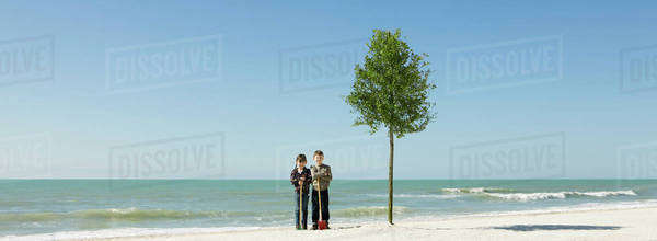 Children standing with shovels beside tree planted on beach Royalty-free stock photo