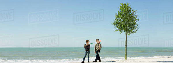 Children standing with gardening tools beside tree planted on beach Royalty-free stock photo