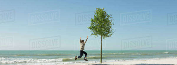Boy jumping in midair on beach Royalty-free stock photo