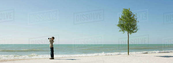 Boy standing on beach, looking at sea with binoculars Royalty-free stock photo