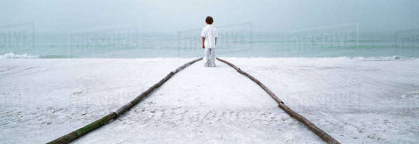 Boy standing at end of footpath on beach, looking at sea Royalty-free stock photo