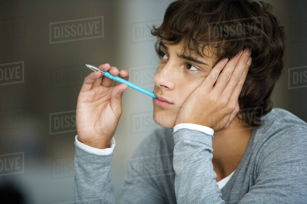Young Man Daydreaming Absently Holding Pen In Mouth
