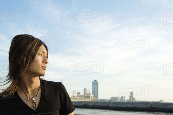 Young Japanese man at waterfront, looking at view, profile Royalty-free stock photo