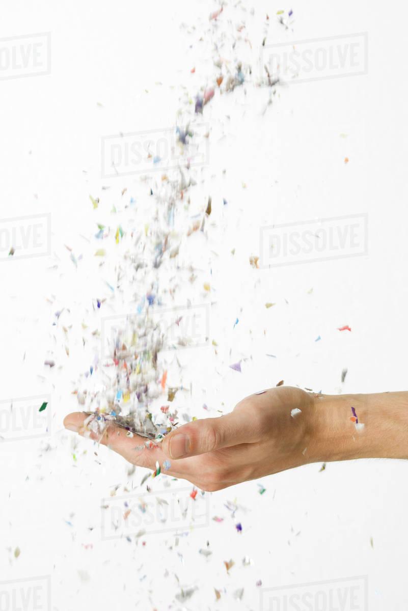 Hand catching falling confetti stock photo