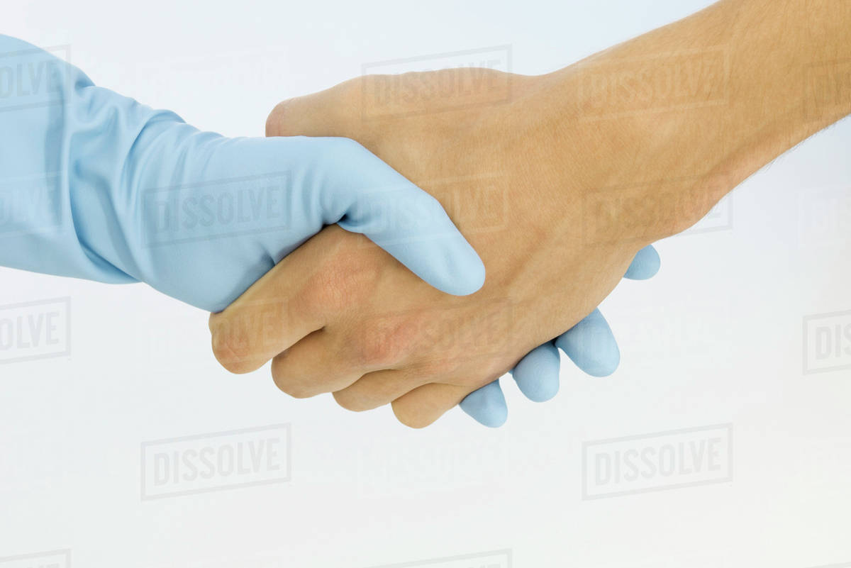 Cropped view of handshake, one hand wearing rubber glove, close-up stock  photo