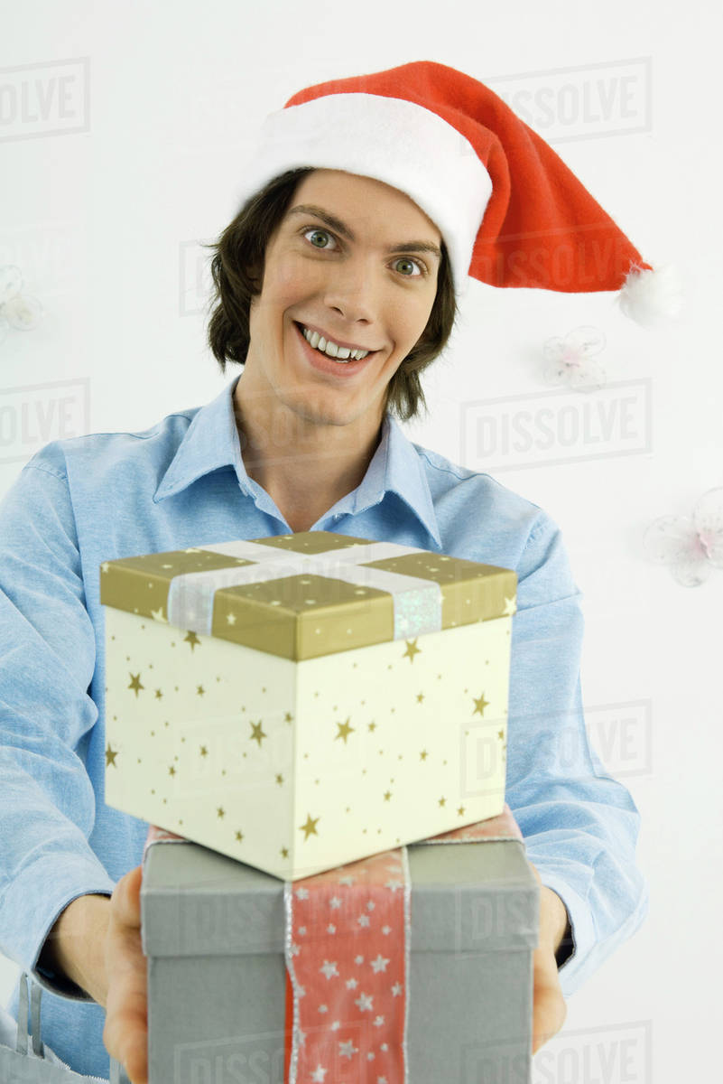 Young man wearing Santa hat holding out Christmas gifts smiling at camera  sc 1 st  Dissolve & Young man wearing Santa hat holding out Christmas gifts smiling at ...