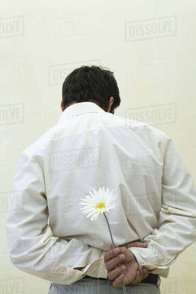 Man holding flower behind his back, rear view Royalty-free stock photo
