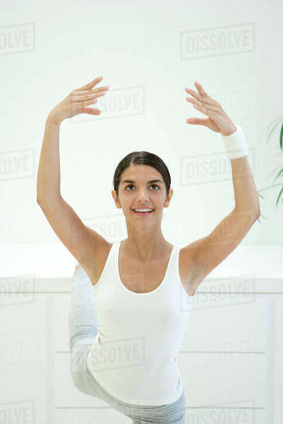 Woman stretching, arms raised and one leg up behind her Royalty-free stock photo