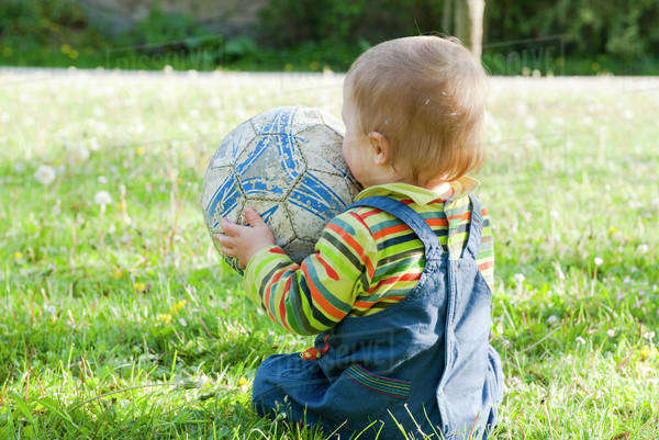 Baby sitting on grass playing with soccer ball, rear view Royalty-free stock photo