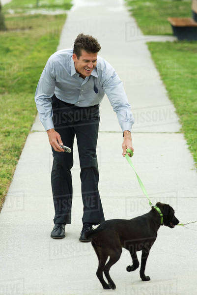 Man walking dog on sidewalk, bending forward, smiling Royalty-free stock photo