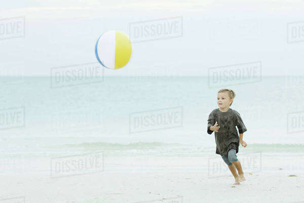 Young boy chasing beach ball at the beach Royalty-free stock photo