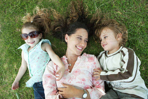 Mother lying on grass with young children Royalty-free stock photo