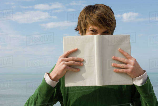Young male holding book in front of face, portrait Royalty-free stock photo