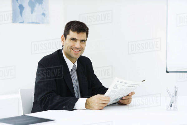 Businessman sitting at desk in office, reading newspaper, smiling at camera Royalty-free stock photo