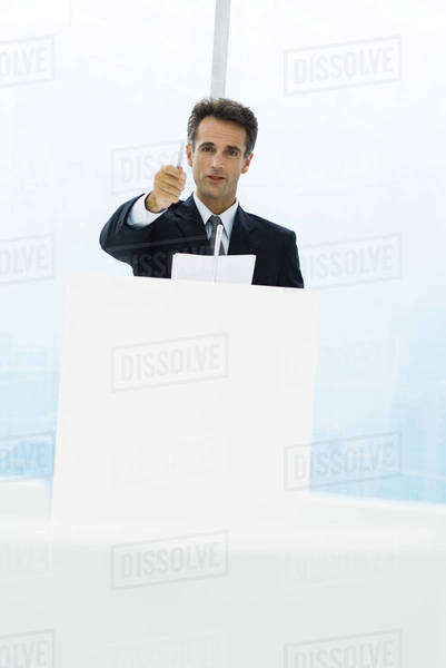 Executive standing behind lectern, pointing with pen at camera Royalty-free stock photo