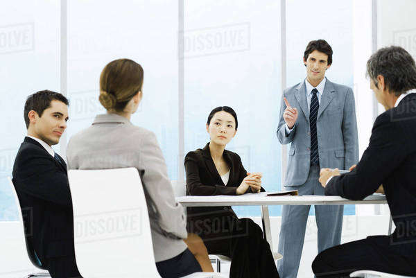 Business associates having meeting, one standing, pointing Royalty-free stock photo