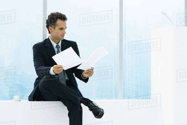 Businessman sitting by window, studying documents Royalty-free stock photo