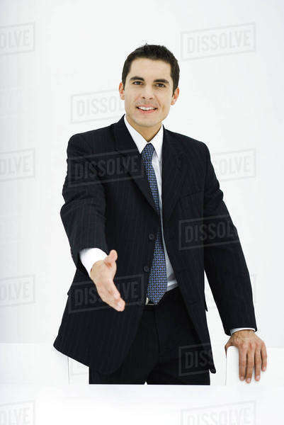 Businessman extending hand toward camera, smiling Royalty-free stock photo
