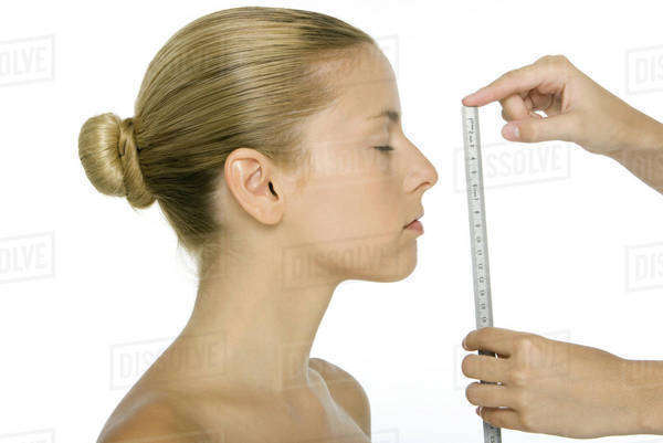 Woman in profile, face being measured with ruler Royalty-free stock photo